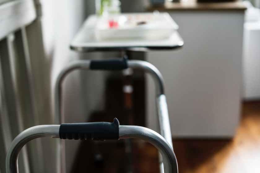 selective focus photo of gray metal folding walker